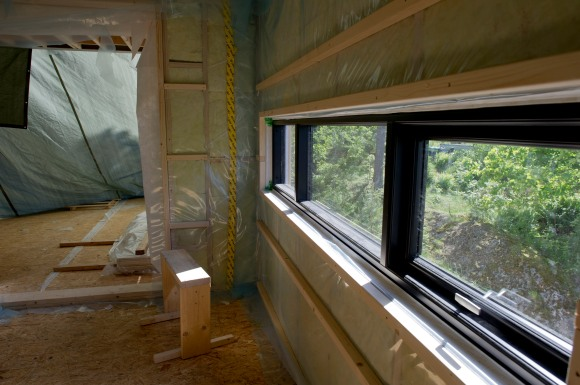 Vindu over kjøkkenbenk. Terrassen er fremdele dekket med presengning da skyvedørene ikke er kommet på plass enda.