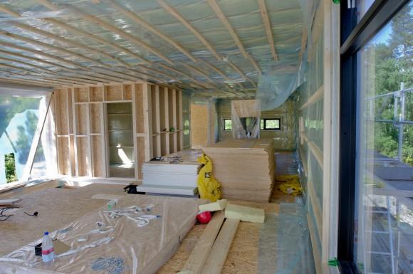 Åpen løsning. Hele overetajsne er åpen mellom kjøkken og stue, bare et lite kontor er lukket inn der trappen kommer opp til venstre i bildet.