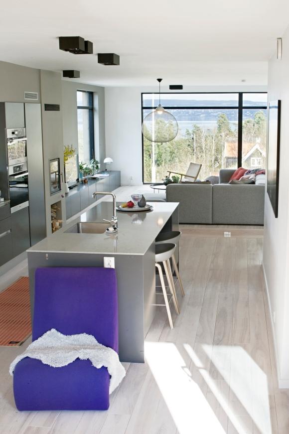 """Kjøkkenøyen er blitt et populært samlingspunkt og barkrakkene fra Hay er det stor kamp om. Den lilla loungestolen i forgrunnen er fra en Verner Panton lenestol som heter """"Amoebe""""."""
