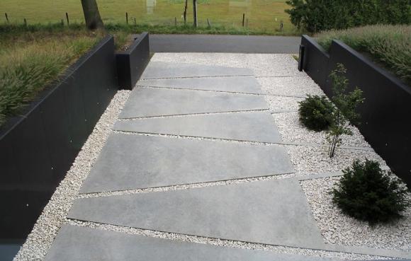 Her er et annet eksempel som viser hvordan man kan skape spennende uterom med å eksprementere med geometriske former og ulike materialer. Digger de sorte betongveggene mot den lyse grusen og de slipte betongflatene som rammer inn buskene på bakken.
